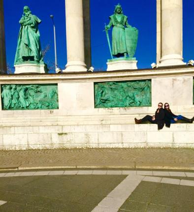 My friend and I sitting in front of the monuments in Heroes' Square, located close to the baths.