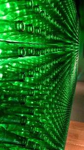 A wall in the Heineken Brewery adorned with Heineken beer bottles.