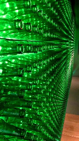 A wall in the Heineken Brewery adorned with Heineken beer bottles.